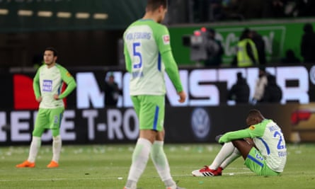 Wolfsburg's Josuha Guilavogui, right, Jeffrey Bruma, centre, and William react after losing to Schalke.