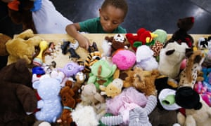 A four-year-old boy picks out a toy from a donations table at the convention in downtown Houston, which has sheltered about a third of the city's displaced people.