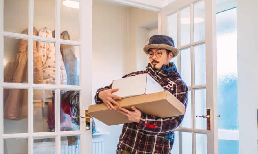 Young handsome Asian man receiving home delivered parcels in new house