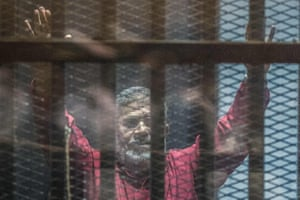 Ousted president Mohamed Morsi, wearing a red uniform, gestures from behind the bars during his trial in Cairo at the police academy in 2014.