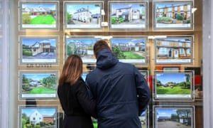 A couple look at houses for sale in the window of William H Brown estate agents
