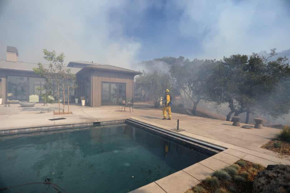 Firefighters work to defend homes from an approaching wildfire in Sonoma, California.