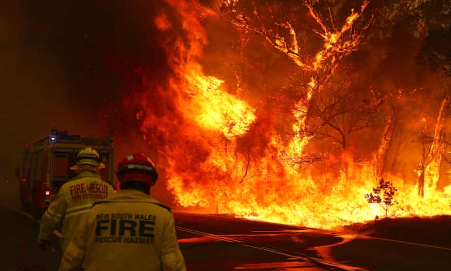 Fire and rescue personal run to move their truck as a bushfire burns next to a major road and homes on the outskirts of the town of Bilpin in Sydney, Australia, December 2019.