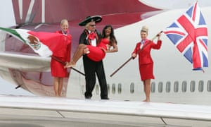 Sir Richard Branson stands on the wing of a virgin airline in a mariachi uniform cradling a woman dressed in red