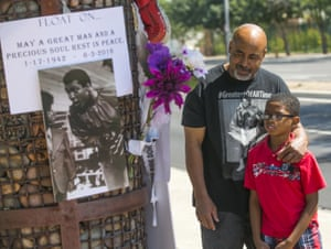 Lynn Boyd Jr. and his son Jayde look at an impromptu memorial for Ali outside the Scottsdale Osborn Medical Center in Scottsdale, Arizona