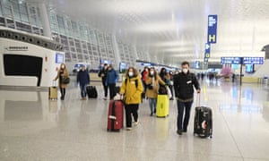 People wear face masks as they walk through the terminal at Wuhan's airport on 1 February 2020.