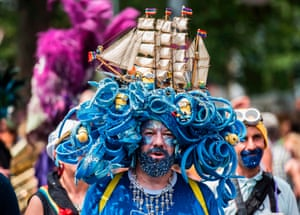 Man in elaborate headpiece featuring model ship and minions