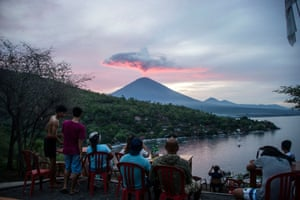 Tourists gather at Amed beach to watch the eruptions. Thousands of foreign tourists were hoping to leave Bali by plane after the airport was reopened