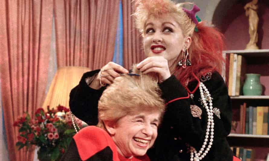 """Sex therapist Dr. Ruth Westheimer cracks up as rock singer Cyndi Lauper does her hair up in """"punk"""" style, in New York, Jan. 17, 1985"""