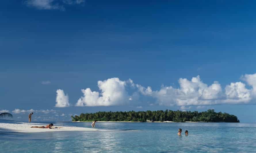 Tourist sunbathing and swimming in the Maldives.