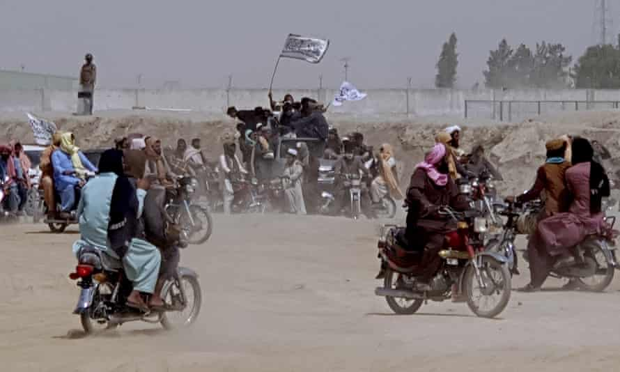 Pro-Taliban Taliban carry white Taliban flags in the Afghan border town of Chaman.