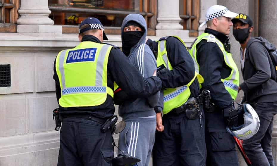 Police stop and search a man in central London in  June