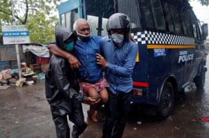 Kolkata, India. Police officers evacuate a disabled resident from a slum, before cyclone Amphan hits the area