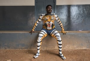 A performer rests after hours of body painting