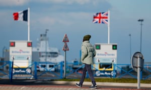 A man walks on February 26, 2018, in front of France and United Kingdom's flags outside the port of Ouistreham, near Caen, Northwestern France