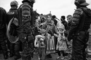 A mother guides her children through a line of Slovenian police at the Timovec border crossing with Croatia. Long delays caused by government travel restrictions produce a build up of tension and anger as people try to continue their journey to Western Europe
