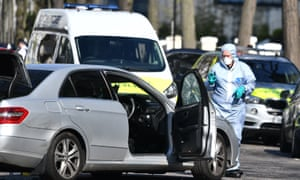Forensics officers examine a damaged car at Holland Park after shots were fired near the Ukrainian embassy.