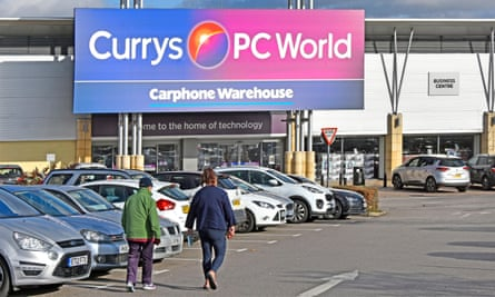 A couple walk through a car park to a Currys PC World and Carphone Warehouse store, indicated by a giant, colourful sign
