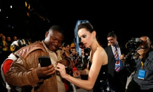 Actress Daisy Ridley signs an autograph for a fan.