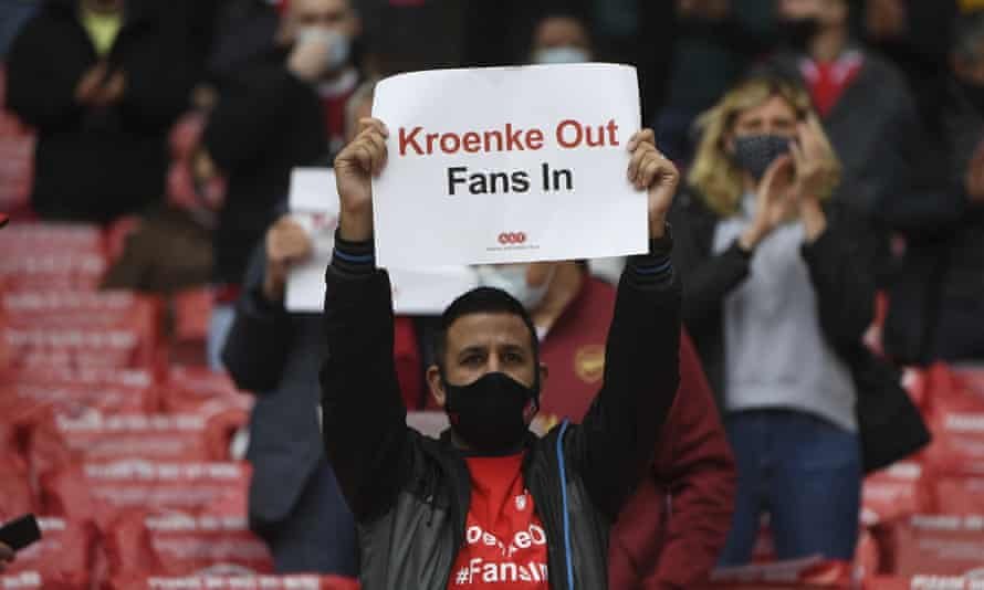 Arsenal fans hold placards calling for owner Stan Kroenke to sell the club.