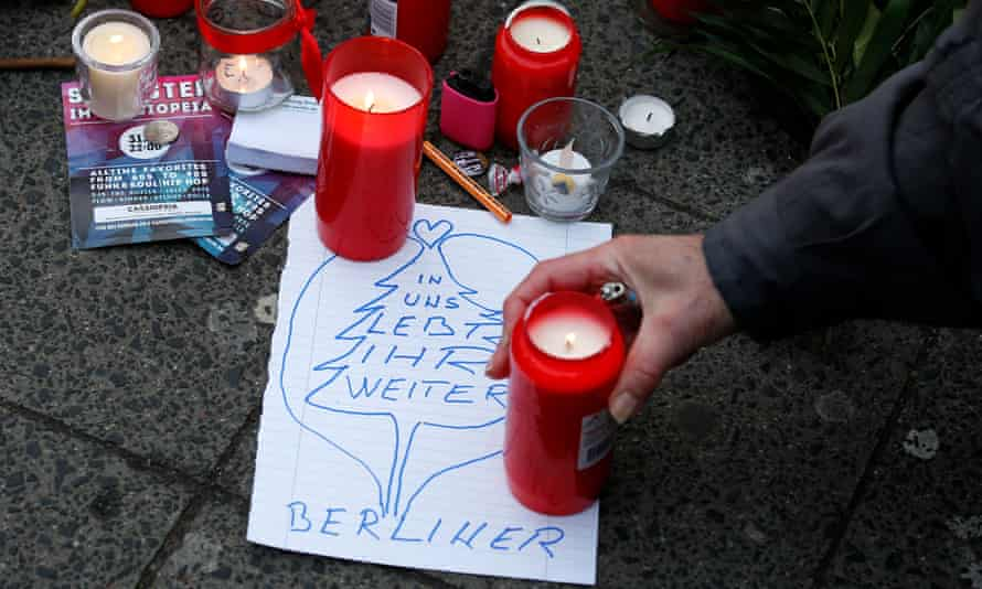 A man lights a candle near the scene, with sign reading: 'You live on in us. Berliners'