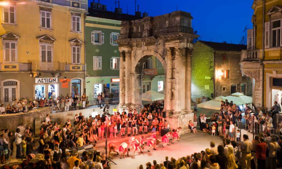 An evening performance taking place beneath the Golden Gate of Pula, Croatia