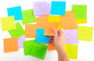 To do list - multicoloured Post-it notes  on white background, with hand choosing one
