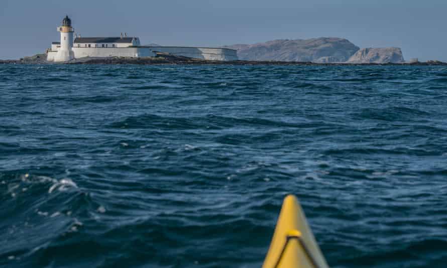 Lighthouse on island, and the prow of a kayak