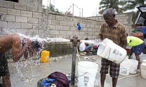 A man takes a shower as another fills a bucket to take home at a public fountain in Tabarre, Haiti.