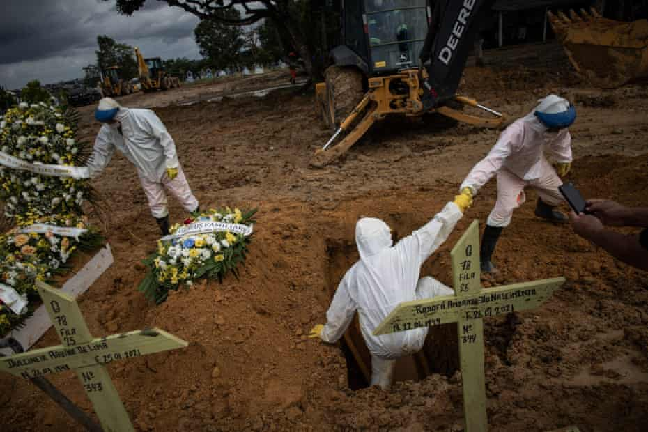 Workers bury a person who died with Covid in Manaus, Amazonas, Brazil, on 27 January.
