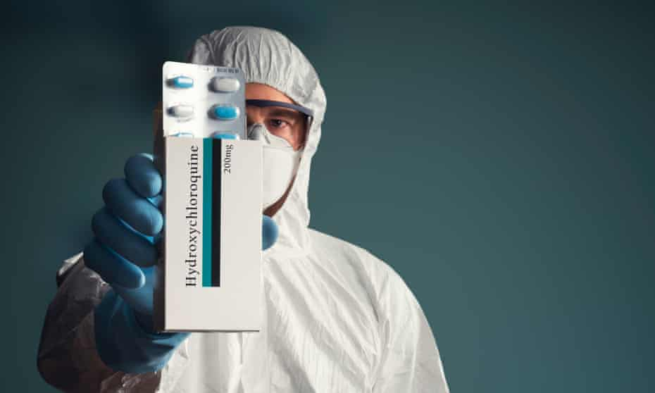A medical worker in full protective suit holding hydroxychloroquine tablets