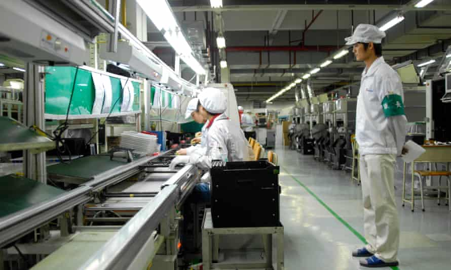 A supervisor watches workers at a Foxconn factory in Shenzhen, Guangdong province.