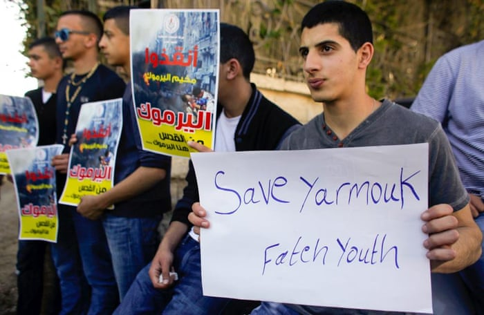 Demonstrators outside the Red Cross building in Jerusalem show support for the Palestinians living in Syria's Yarmouk refugee camp on Monday