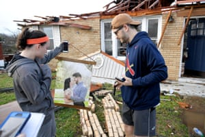 Meg Selby and Mac Warren look at their engagement photo, found in their damaged house in Stanford Estates.