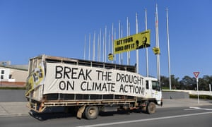 Greenpeace activists protesting against climate change unfurl a banner on the flagpoles outside Parliament House on Monday.