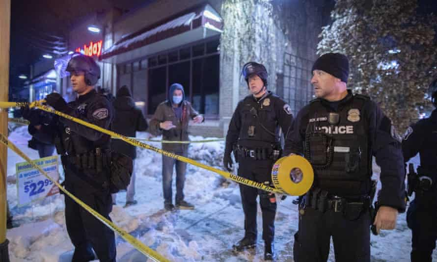 Police put up fresh tape outside the Holiday gas station where someone was killed by police, 30 December 2020,