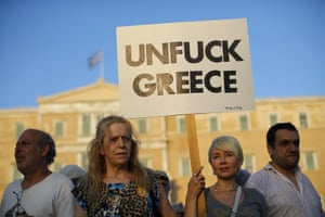 A protester holds a banner during a pro-government rally calling on Greece's European and International Monetary creditors to soften their stance in the cash-for-reforms talks in Athens, June 17, 2015.The Greek central bank warned on Wednesday that the country risked a painful exit from the euro and ultimately even the European Union if Athens and its creditors do not strike a swift aid-for-reforms deal. REUTERS/Paul Hanna