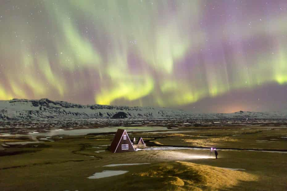 An aurora hunter photographs a traditional house lit by the northern lights.