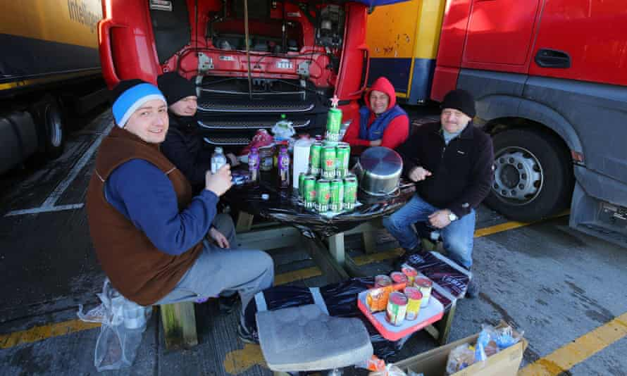 Polish lorry drivers, with a makeshift Christmas tree made out of empty Heineken cans, share Christmas Day food and drinks near Folkestone, Kent.