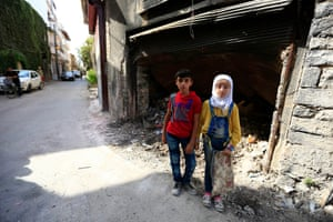 Bassam and Hamida, 12-year-old twins from the old city of Homs in the Syrian Arab Republic, stand near garbage outside a dilapidated building on 13 September 2015