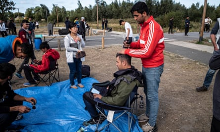 Asylum seekers in Calais with facilities provided by charity workers enabling them to have a hair cut.