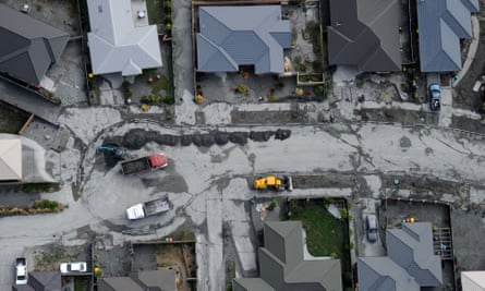 A suburban street is cleaned of silt from liquefaction in Christchurch
