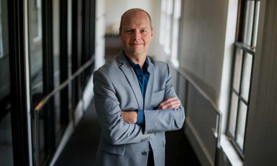 a suited sebastian thrun in shirt collars standing with his arms folded in a corridor