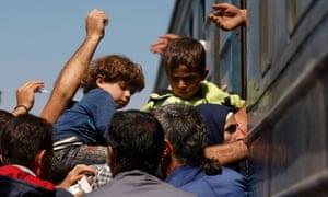Migrants board a train