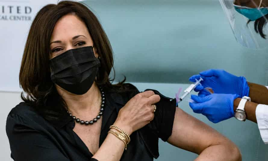 Kamala Harris in a mask rolling up a sleeve to receive a vaccination