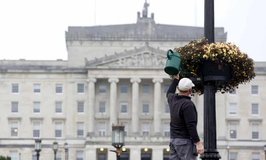 A gardener waters flowers in front of the Northern Ireland assembly buildings at Stormont