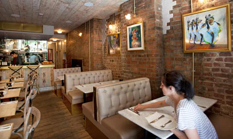 Banquettes, brick walls and a bar at Petit Pois Bistro, where a waitress with hair in a ponytail is setting a table