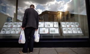 A man looks at flats to rent in the window of an estate agency