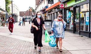 Two women in face masks carrying shopping bags along a pedestrianised shopping street