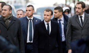 The French president, Emmanuel Macron, flanked by the interior minister Christophe Castaner (R), inspects the aftermath of Saturday's clashes in Paris.